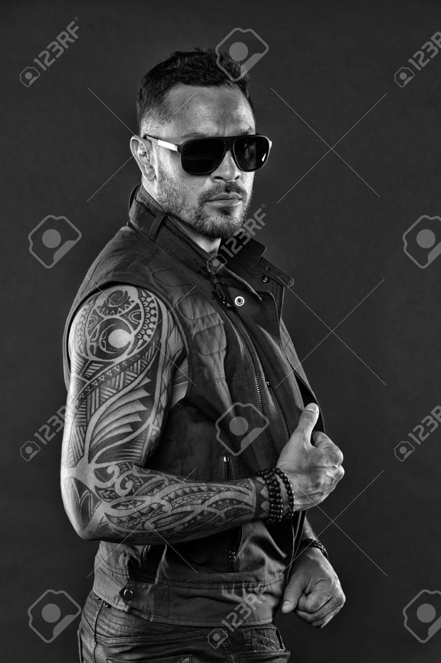 6d6ab5538 Tattooed man with biceps and triceps. Tattoo model with beard on unshaven  face. Bearded man with tattoo on strong arms. Fashion macho in trendy  sunglasses.