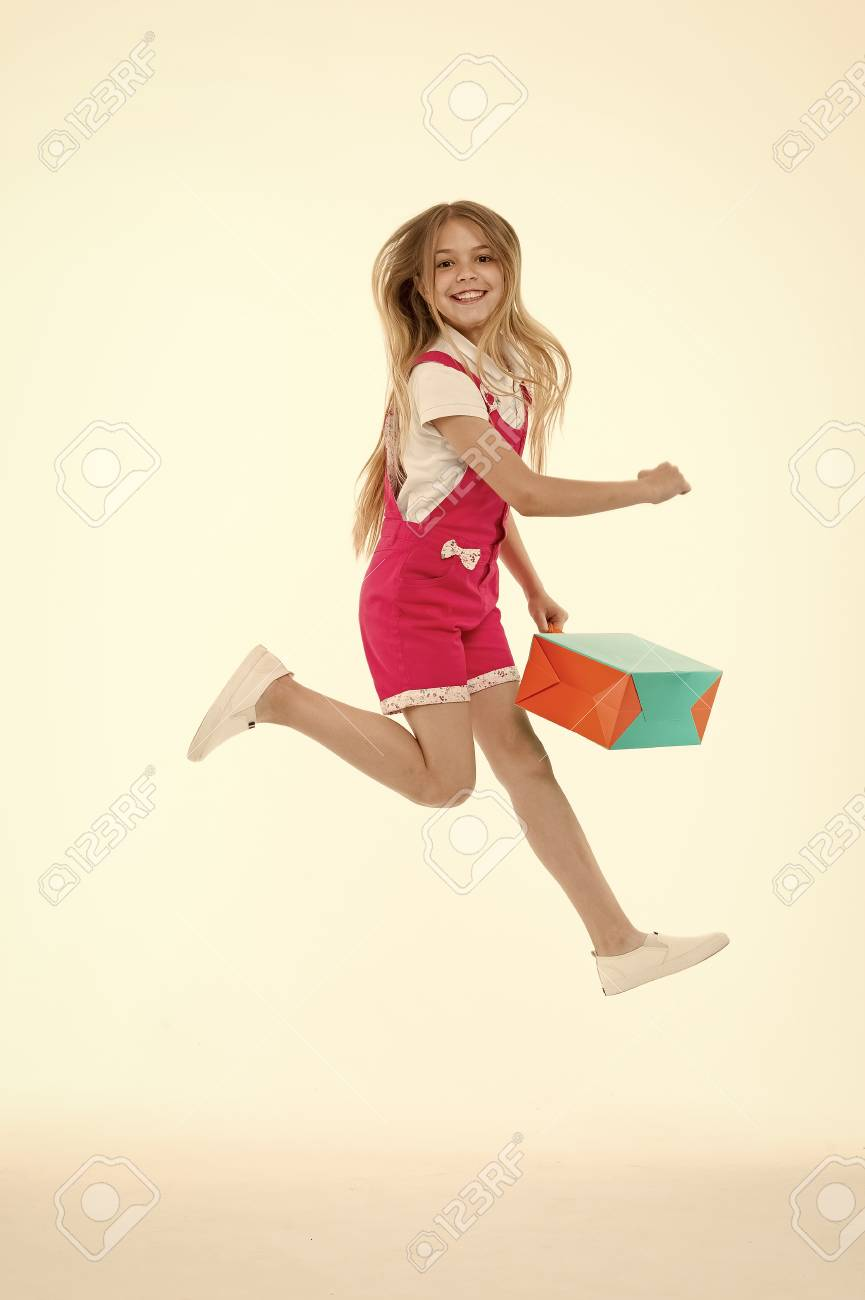 4f4ac7b1 Happy girl jump with shopping bag isolated on white. Little child smile  with paper bag