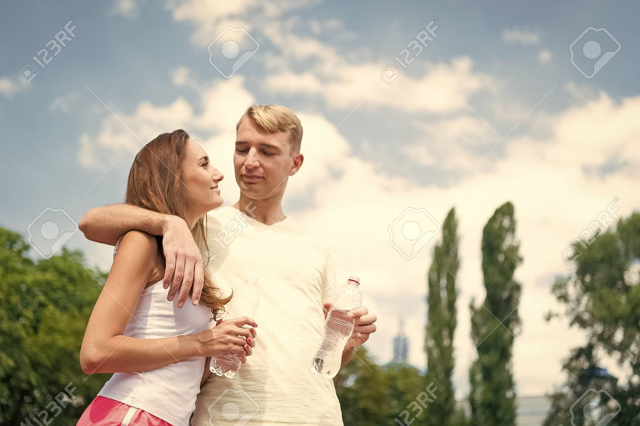 Woman and man drink water from bottle. Girl and guy sunny outdoor. Summer activity and energy. Couple of coach relax after workout. Sport and health. - 125008830