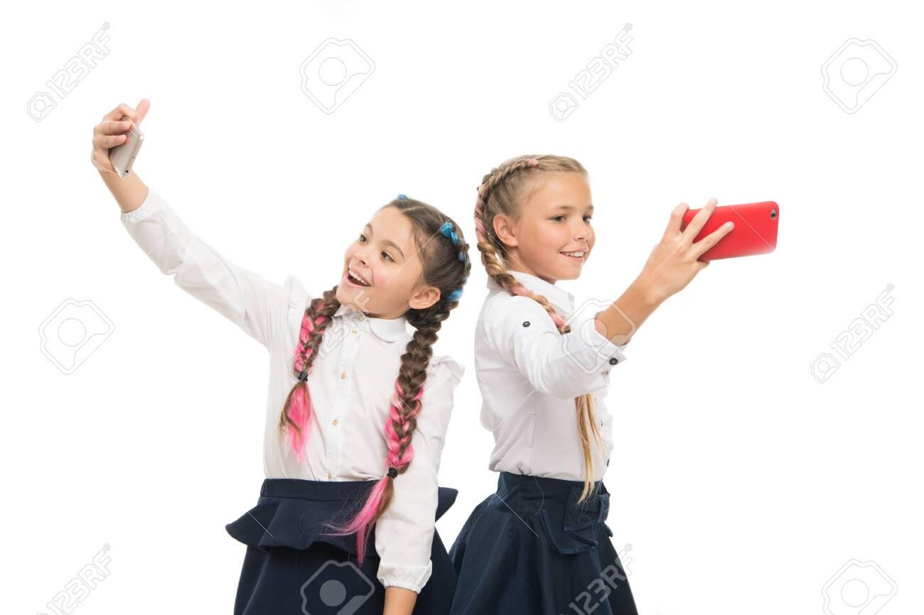 True selfie stars. Happy small schoolgirls taking selfie with smartphones isolated on white. Little children smiling to selfie cameras in mobile phones. Enjoying selfie session on september 1 - 129243277