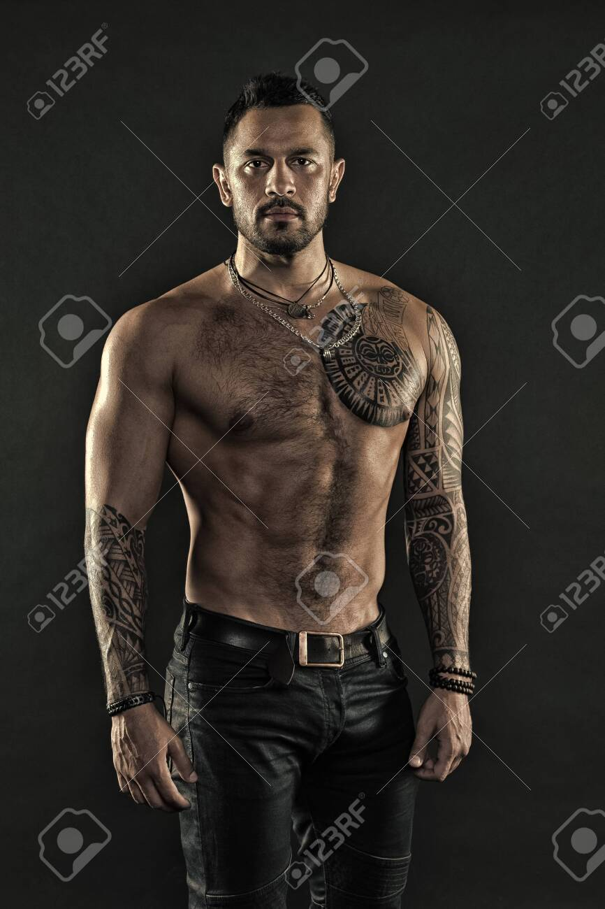 Tattoo art. Handsome fit man posing wearing in jeans with tattoo. Man handsome shirtless muscular with jeans over dark background. Muscular tattooed athlete look attractive. Sport and fashion concept - 135261552
