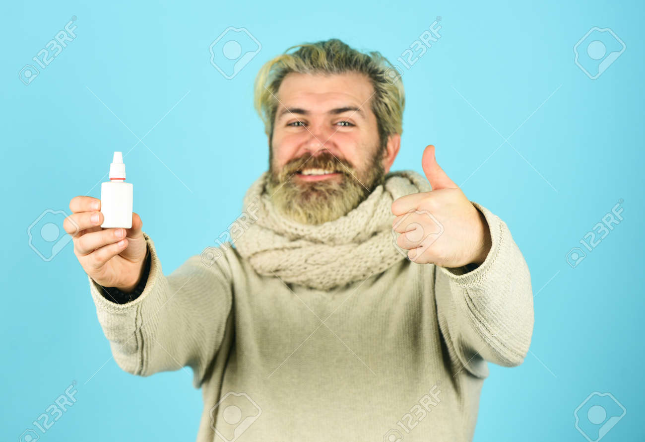 Runny nose recovery. Health care concept. Fast recovery. Cold flu remedies. Runny nose and symptoms of cold. Man scarf hold nasal spray. Medicines effective recovery. Recommended medical treatment - 156665816