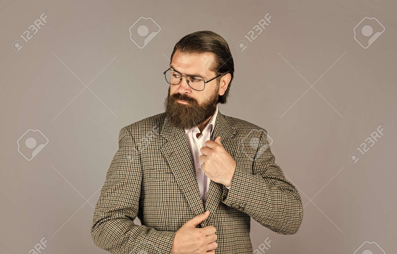 serious bearded man. handsome and successful man in expensive suit. He is in white shirt and glasses. stylish successful man in suit posing. business man wear suit. official office lifestyle - 157516974