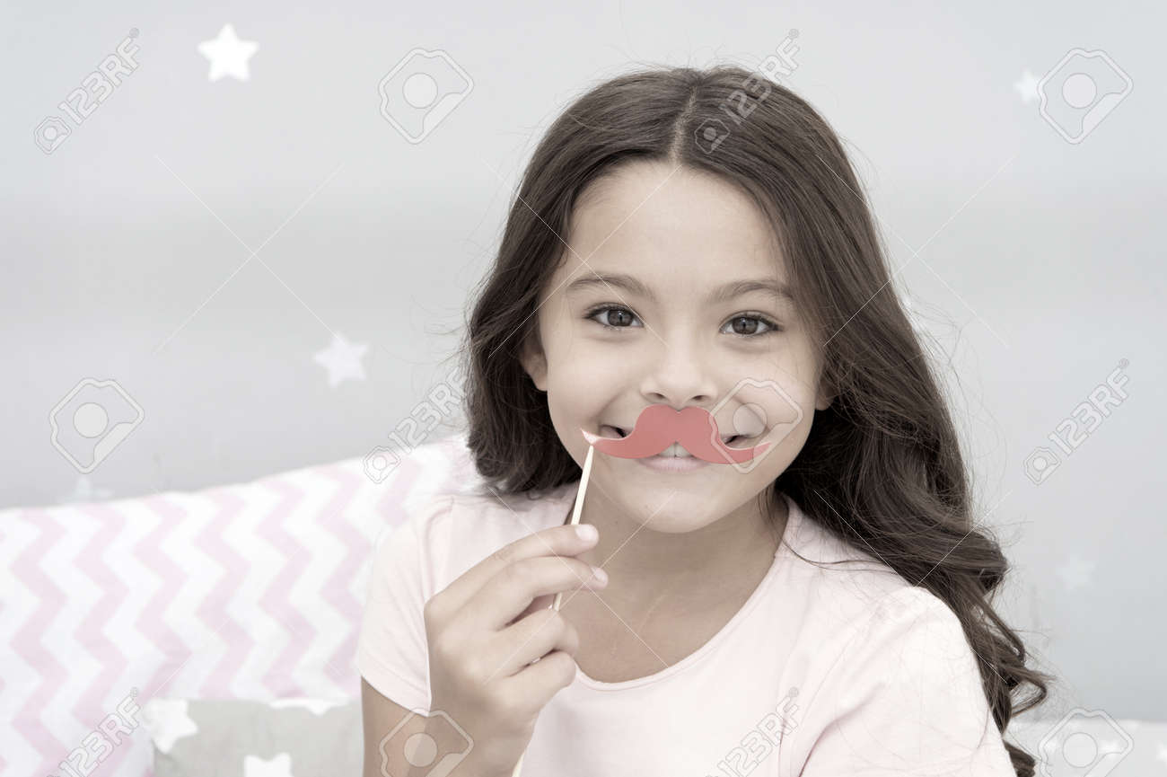 Having fun with face mustache. Happy small girl. Small girl hold fake mustache on face. Happy childhood. My childhood is amazing - 157868038