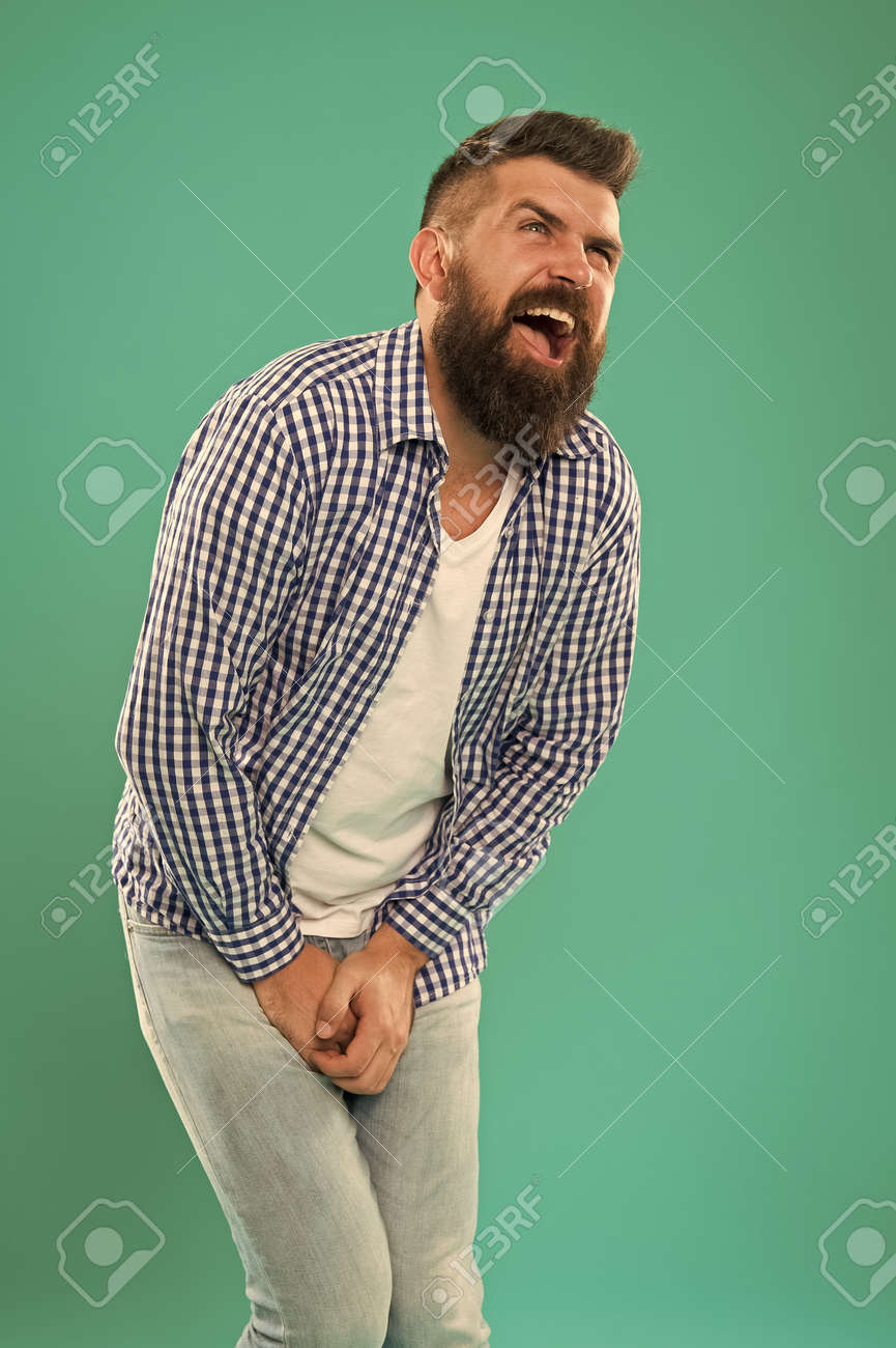 Testicular Blow. Guy got hit in the crotch. Guy folds himself while trying to deal with the pain. Sharp pain that incapacitates your whole body. Bearded man suffering. Attacked - 164026967