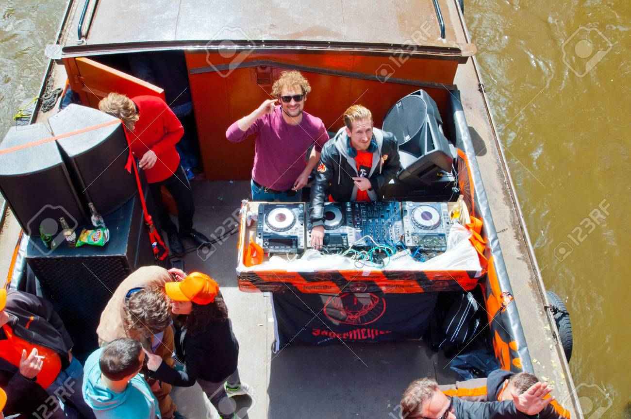 AMSTERDAM NETHERLANDS APRIL 27  DJ plays music on boat party on Amsterdam  canal during King39s. AMSTERDAM NETHERLANDS APRIL 27  DJ Plays Music On Boat Party