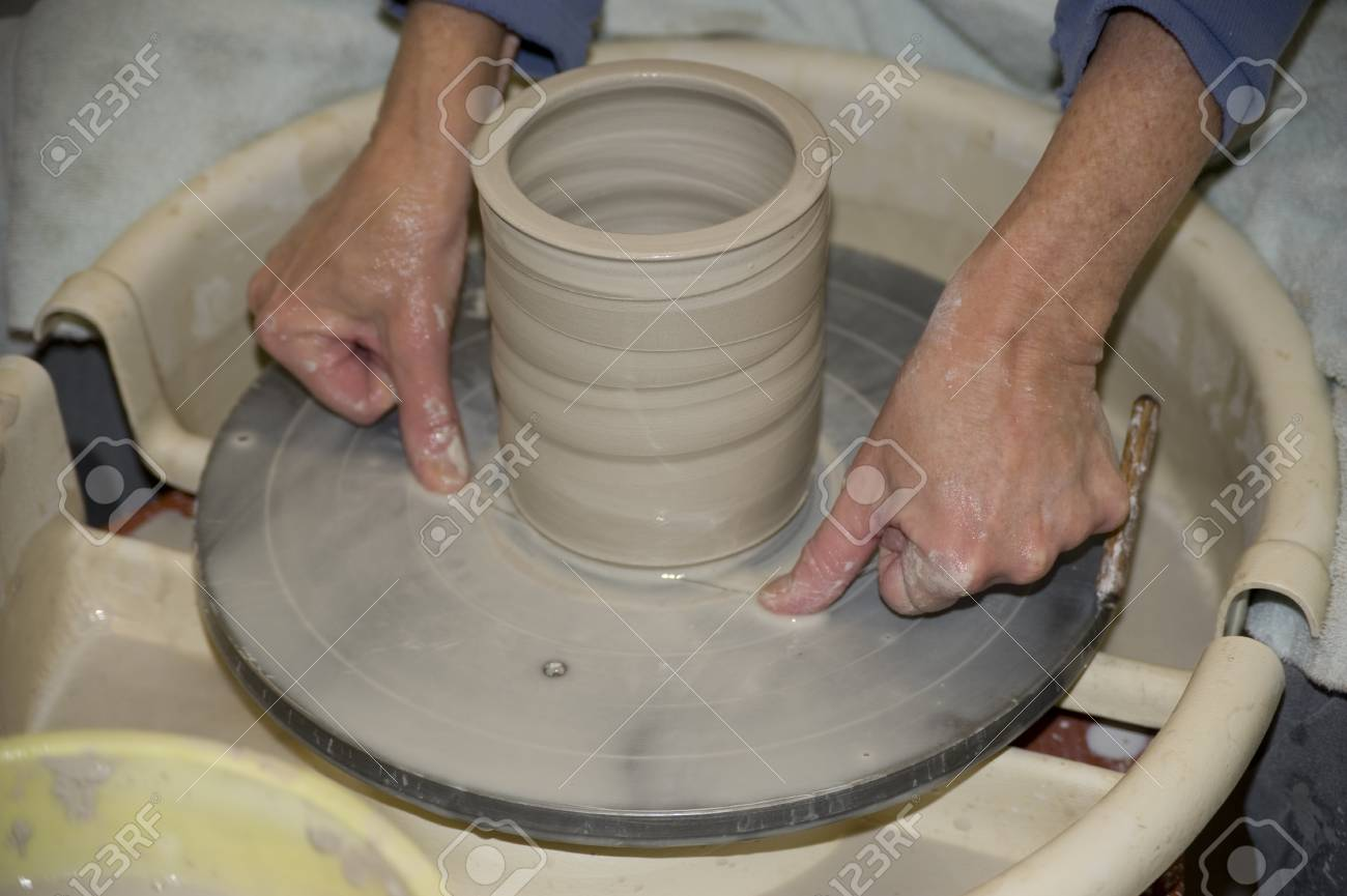 A Talented Potter Finishes The Process Of Throwing A Clay Pot ...