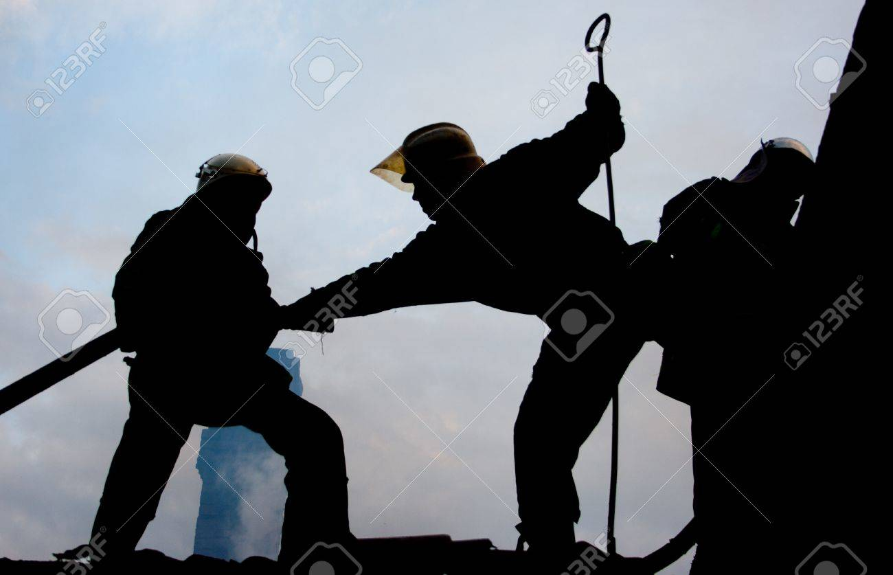 Silhouette of two firemen fighting a raging fire with huge flames of burning scrap timber Stock Photo - 14416364