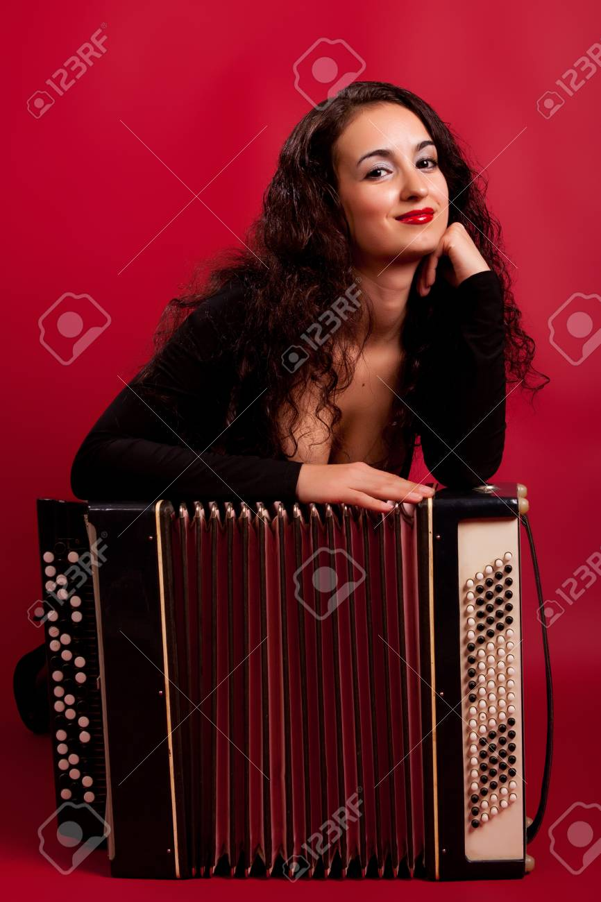 beautiful young brunette in an elegant dress with accordion