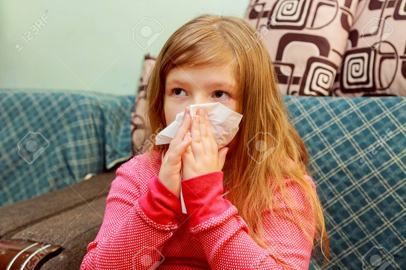 Little girl blows his nose in a paper tissue sick child wiping his nose - 69335232