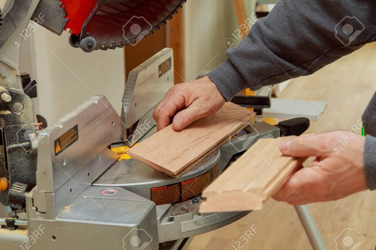 bauarbeiter, trimmen parkett auf kreis gehrung mit säge zum