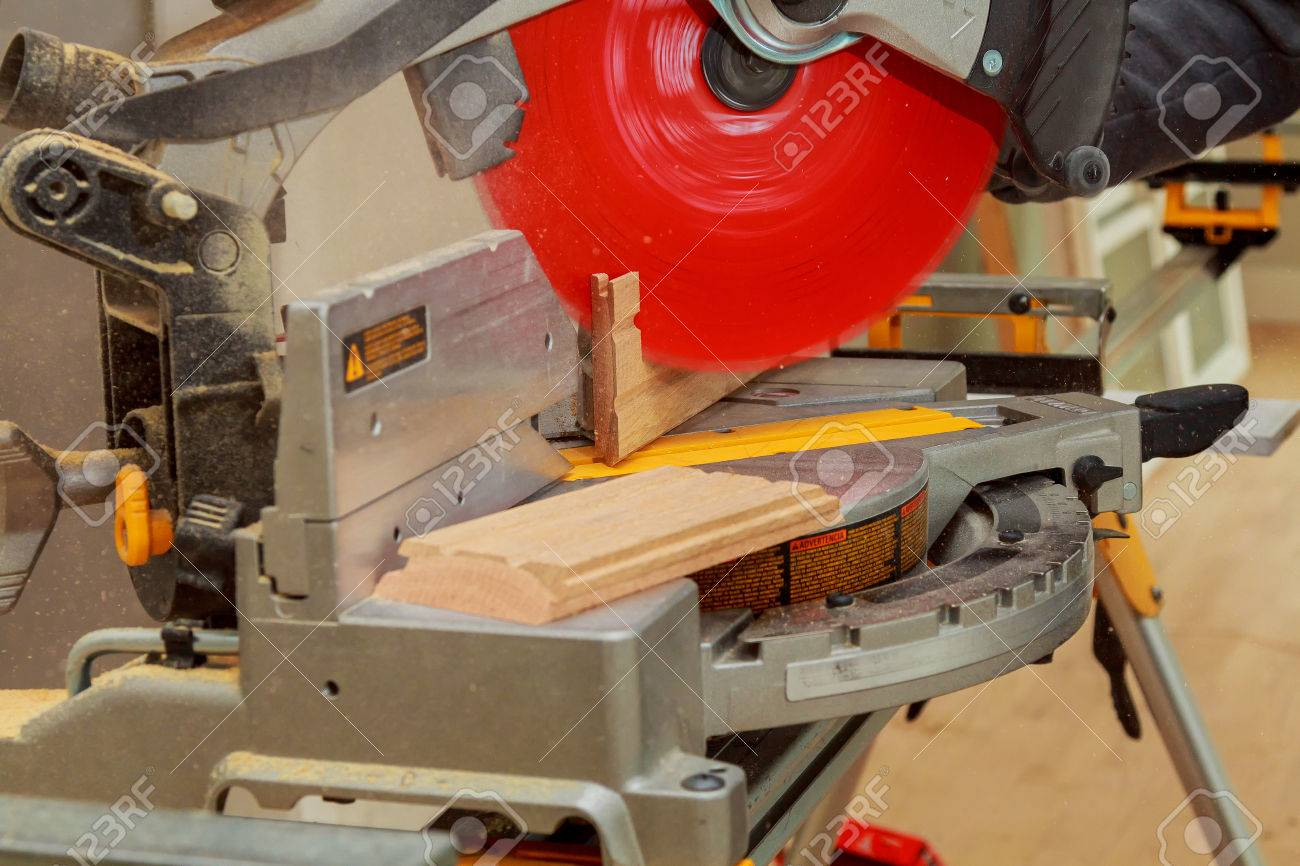mann schneidet holz auf elektrische säge für das schneiden von