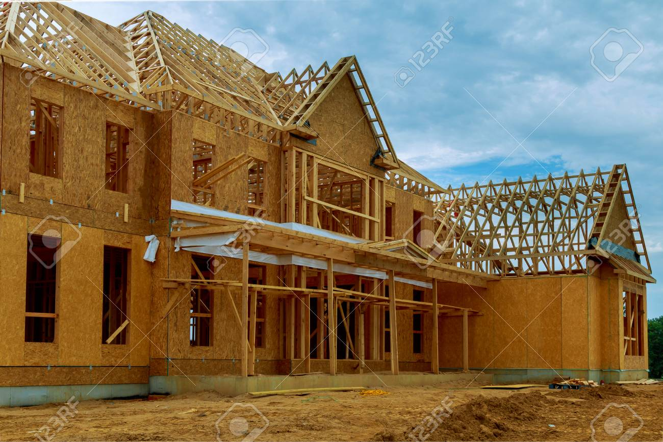 A new wooden house under construction in a blue sky - 80937370