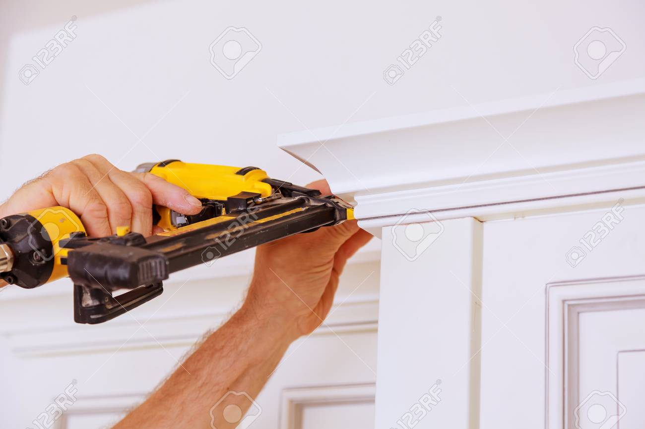 Carpenter Brad Using Nail Gun To Crown Moulding On Kitchen Cabinets