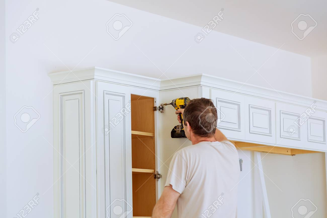 technician man installing kitchen cabinets Installation of kitchen..