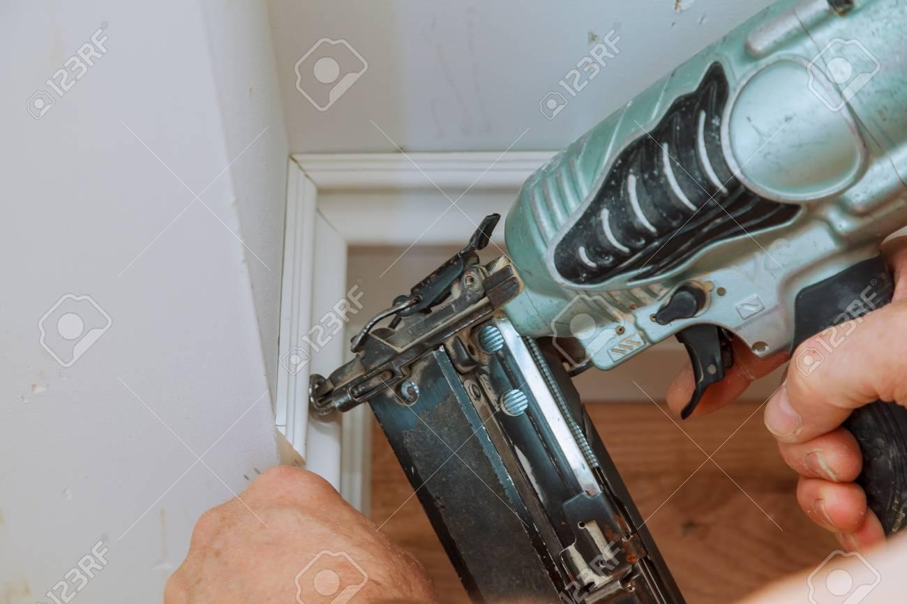 Carpenter Brad Using Nail Gun To Moulding Framing Trim, With.. Stock ...
