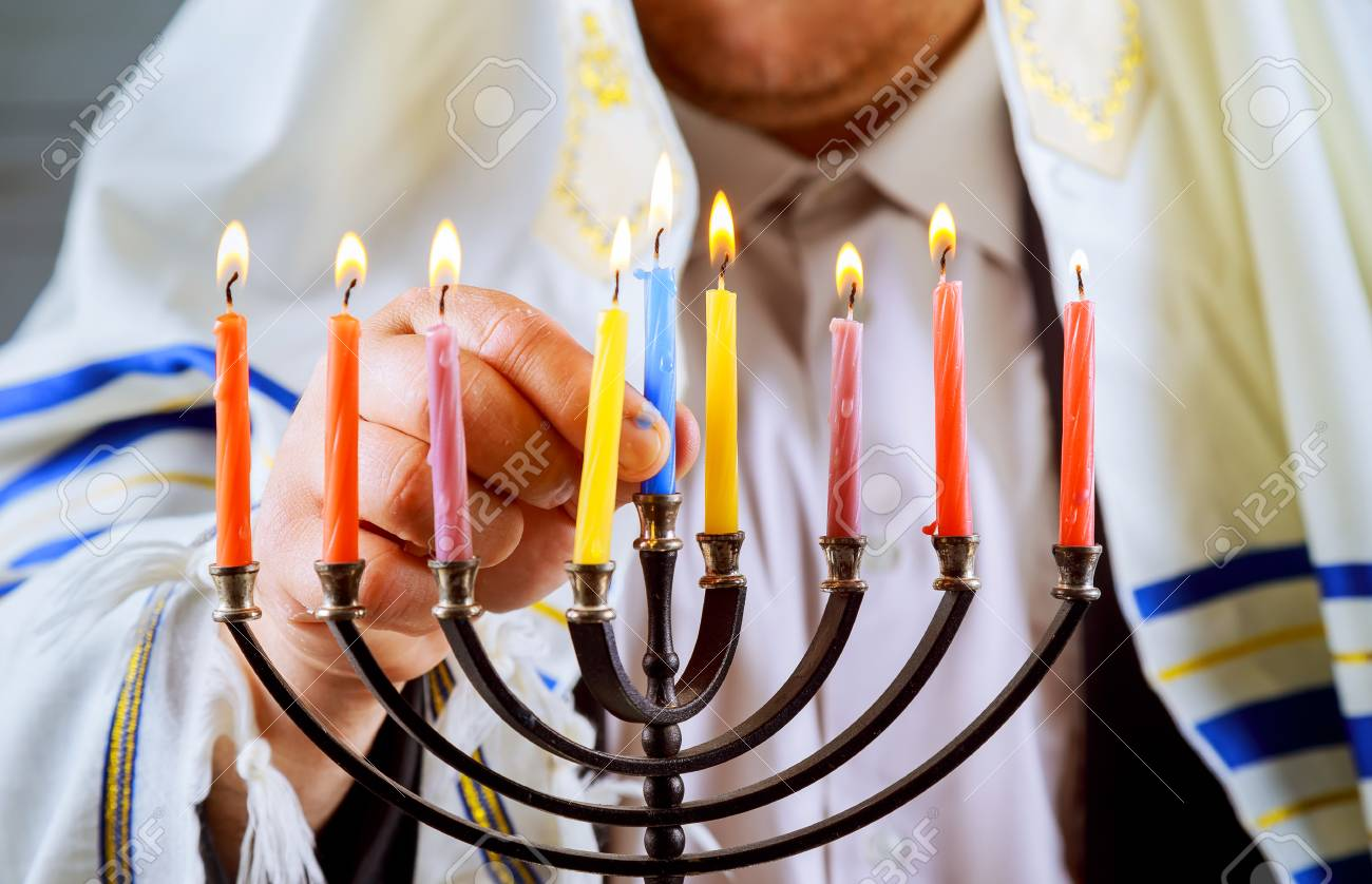 Jewish Candle Lights Male Hand Lighting Candles In Menorah On Table Served  For Hanukkah Stock Photo