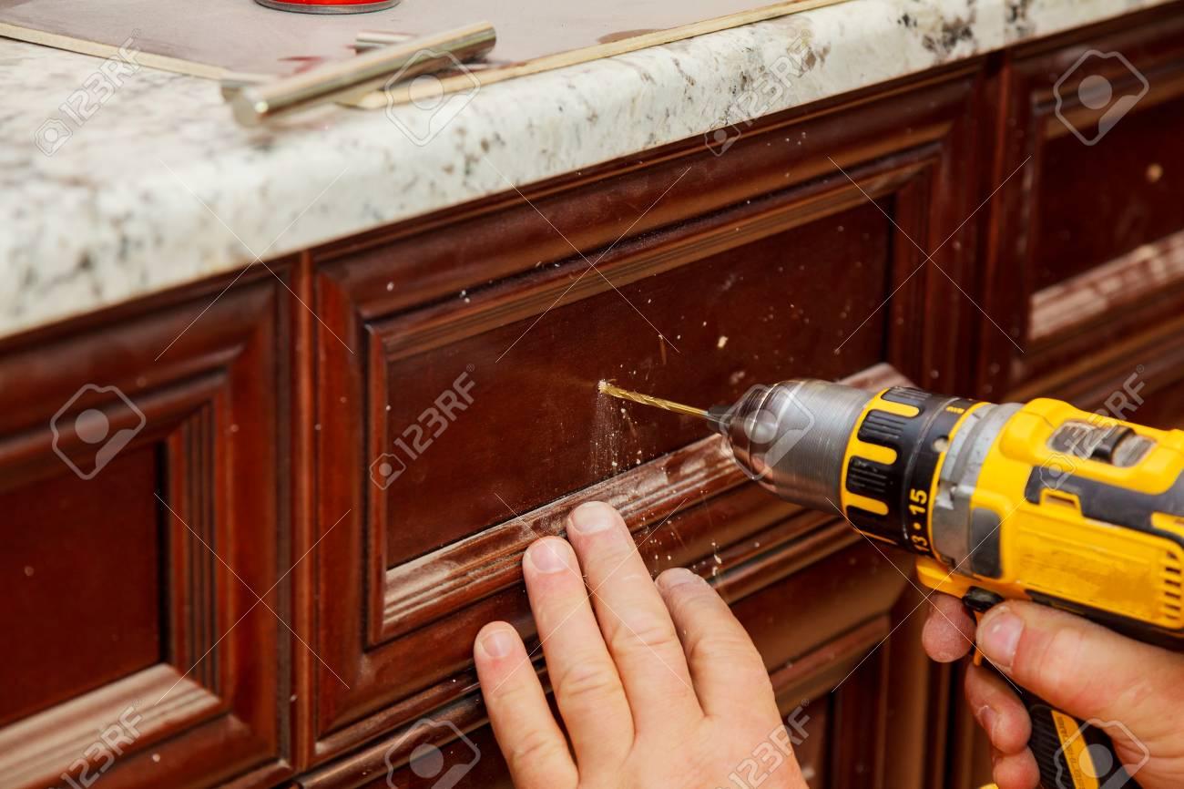 master drills the door in the cabinet door - 90134687