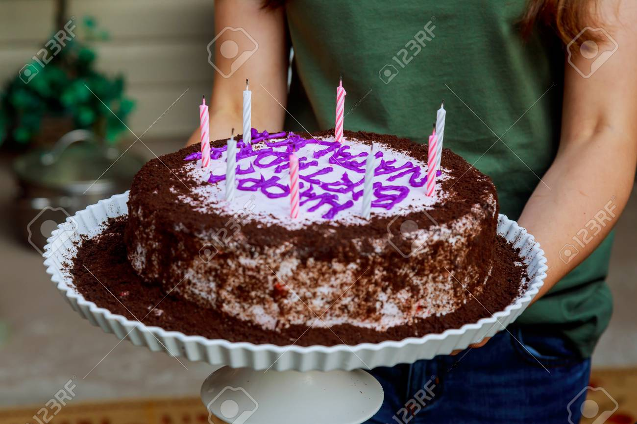 Young Woman Holding Plate With Tasty Birthday Cake Against Defocused
