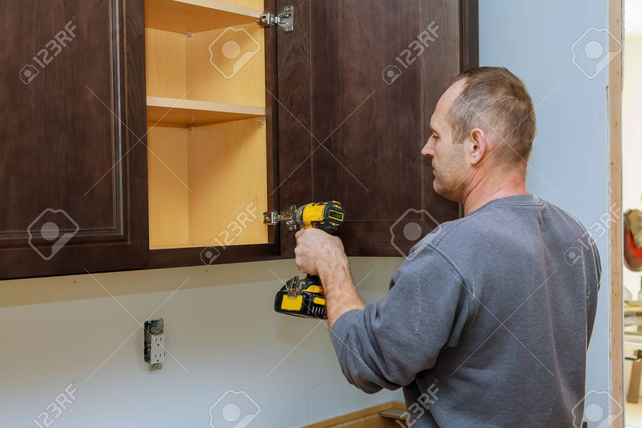 Handyman Fixing Kitchen's Cabinet With Screwdriver Adjusting.. Stock ...