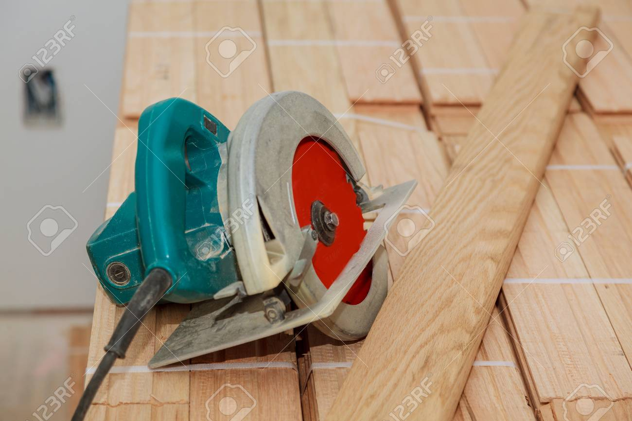 Electric saw on wood floor in progress cut old parquet floor with electric saw - 92783024