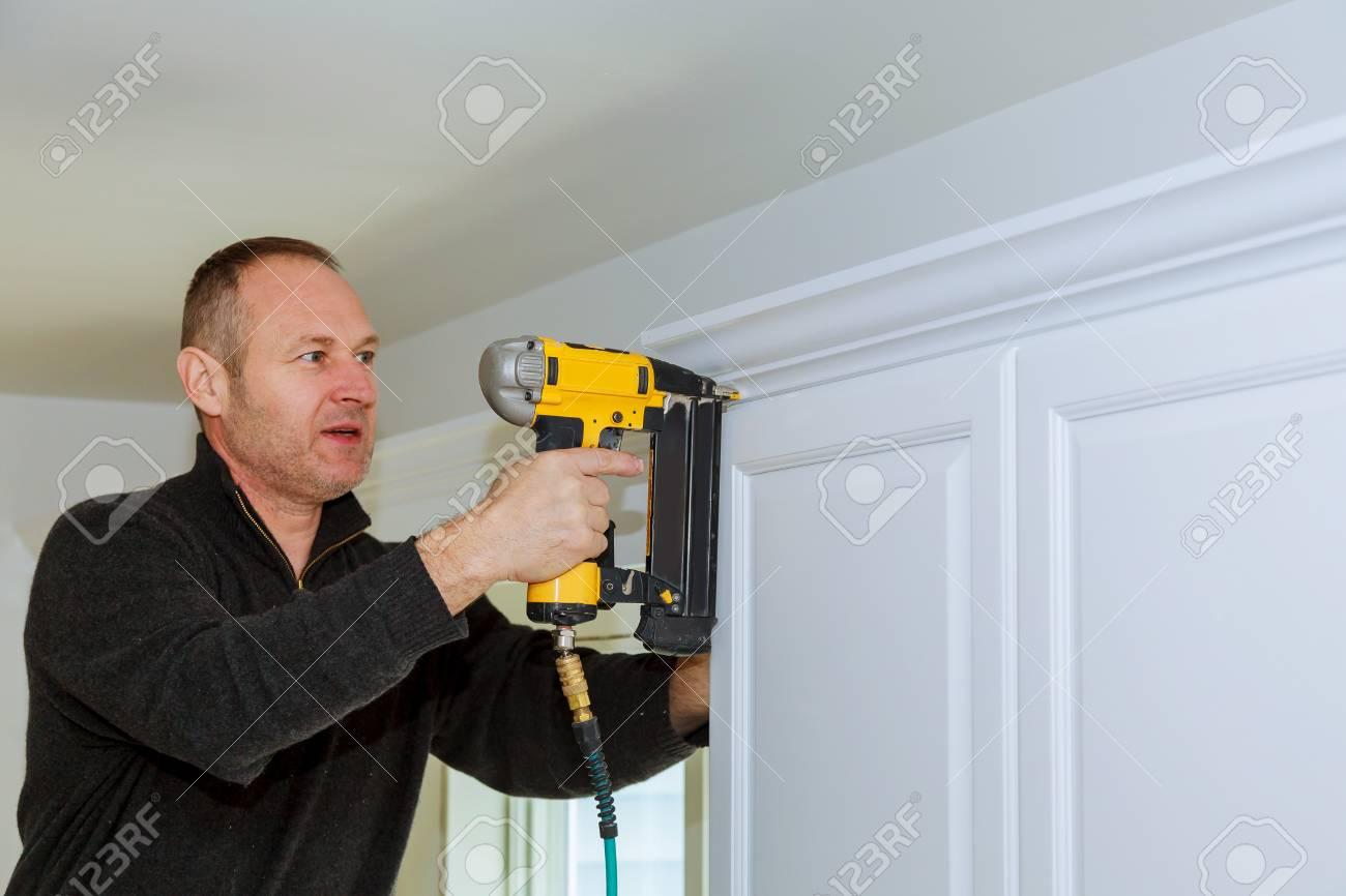 Handyman Working Using Brad Nail Air Gun To Crown Moulding On ...