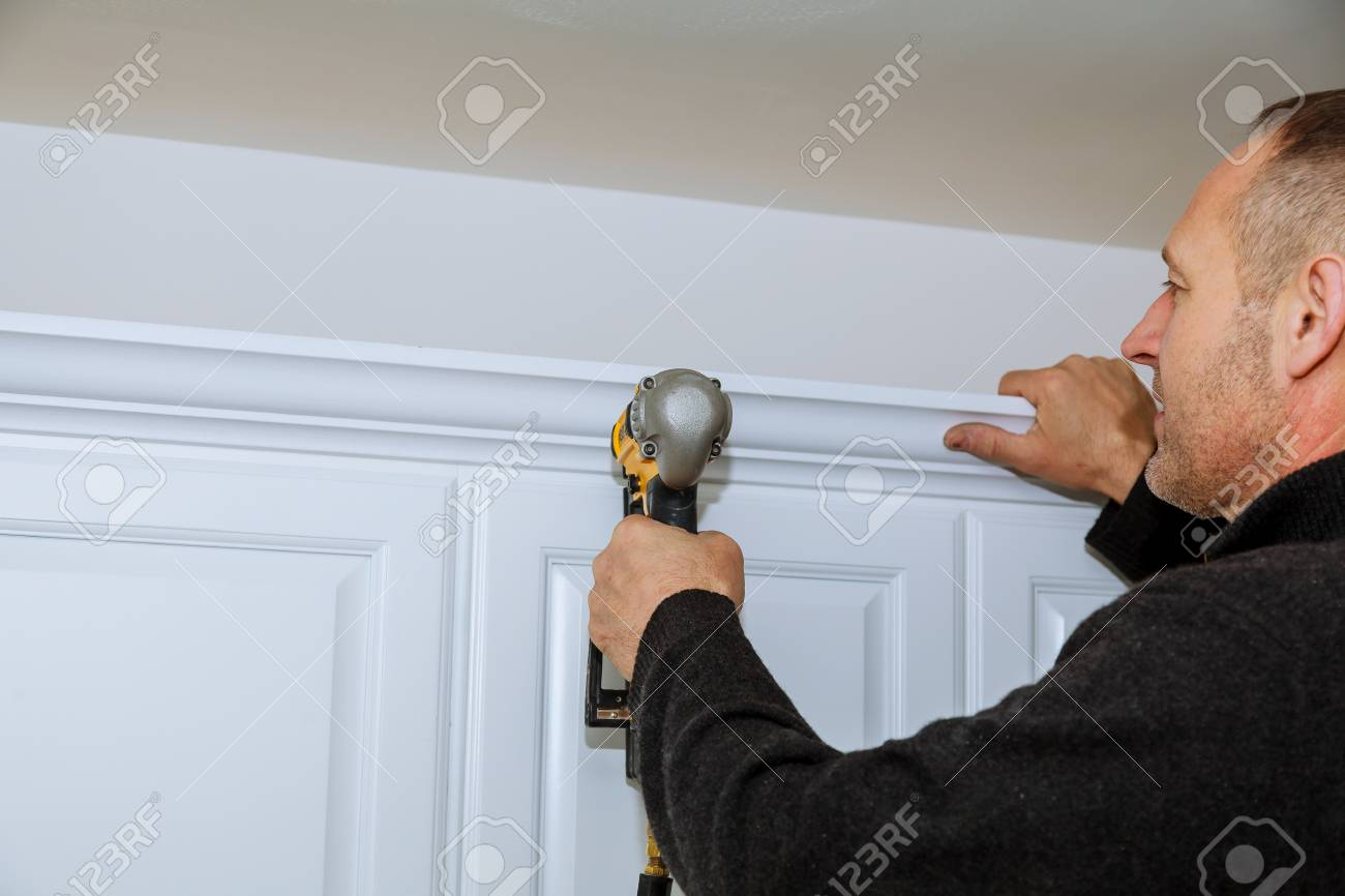 Handyman Using Brad Nail Gun On Installation Crown Moulding Wall