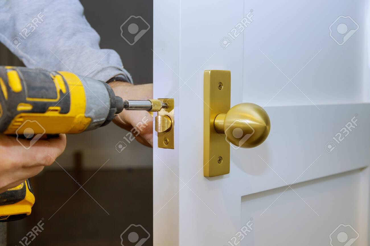 Close up of installation of the door lock with a screwdriver - 142916411