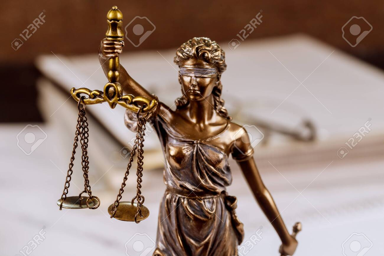 Statue justice scales law lawyer pile of unfinished documents on law office desk - 143389236