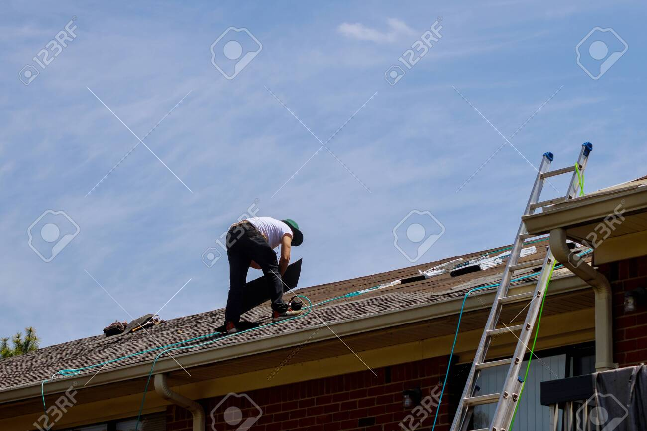 Roof repair, worker with replacing gray tiles shingles on house being applied - 147052870