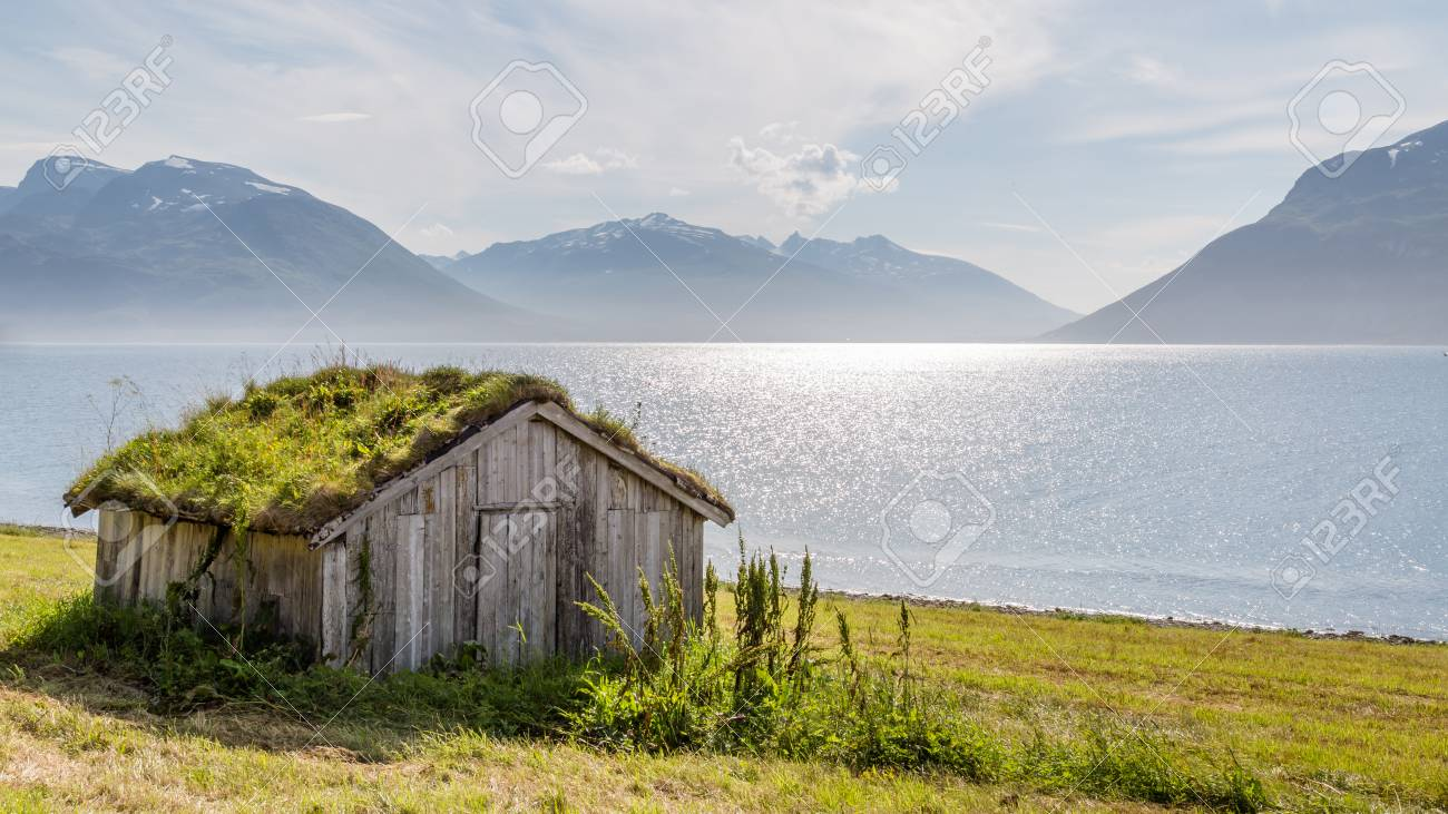 Typical Scandinavian landscape with an old hut with a green roof along a lake - 64630602