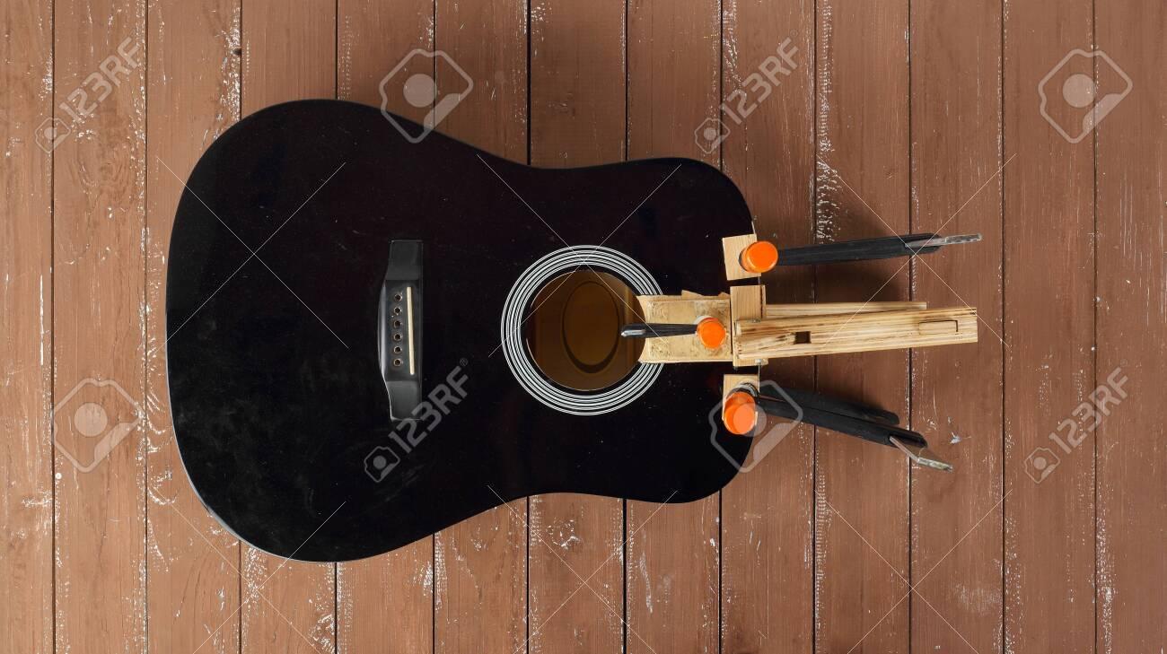 Guitar repair and service - Repair clamping broken sound board acoustic guitar top view wooden background - 128715141