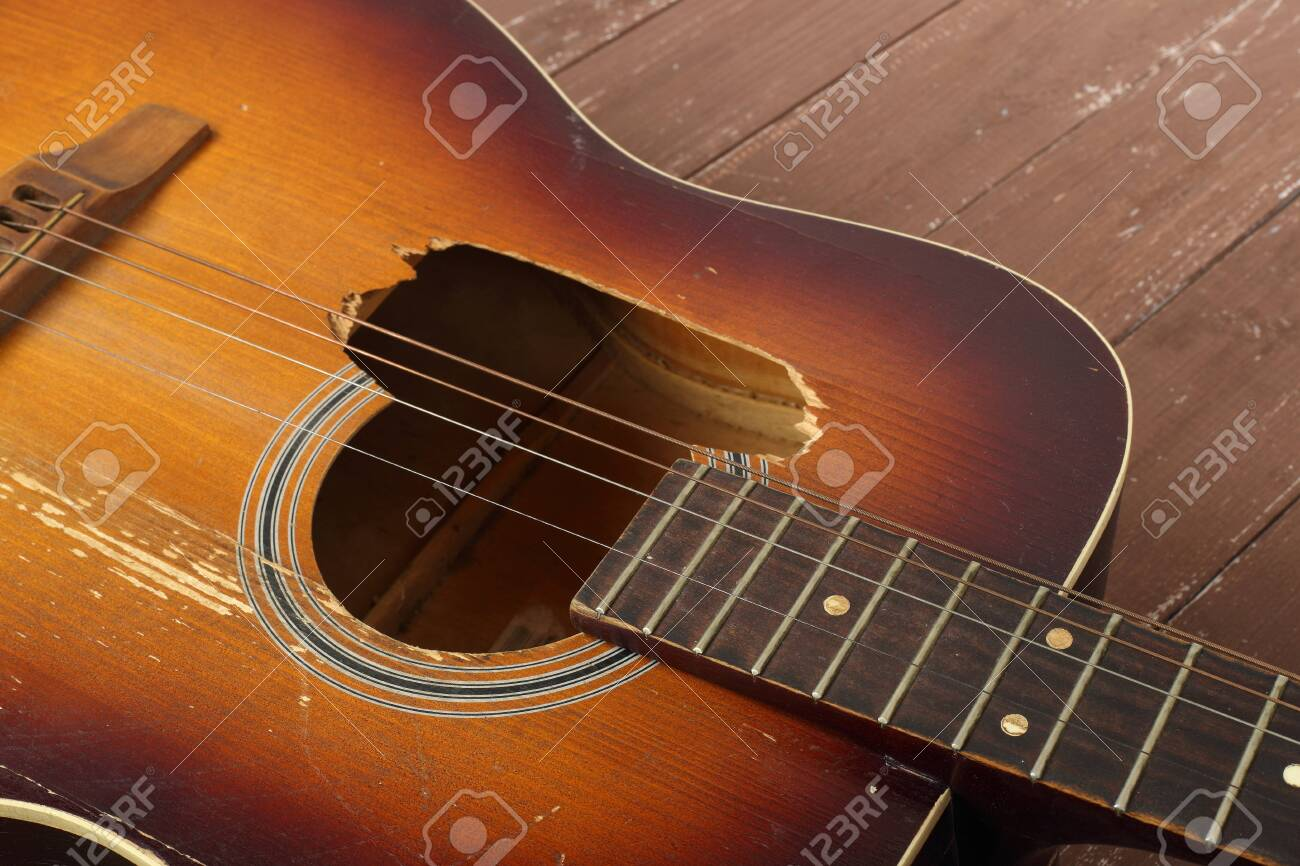 Musical instrument - Closeup fragment broken classic acoustic guitar on a wooden background. - 144839391