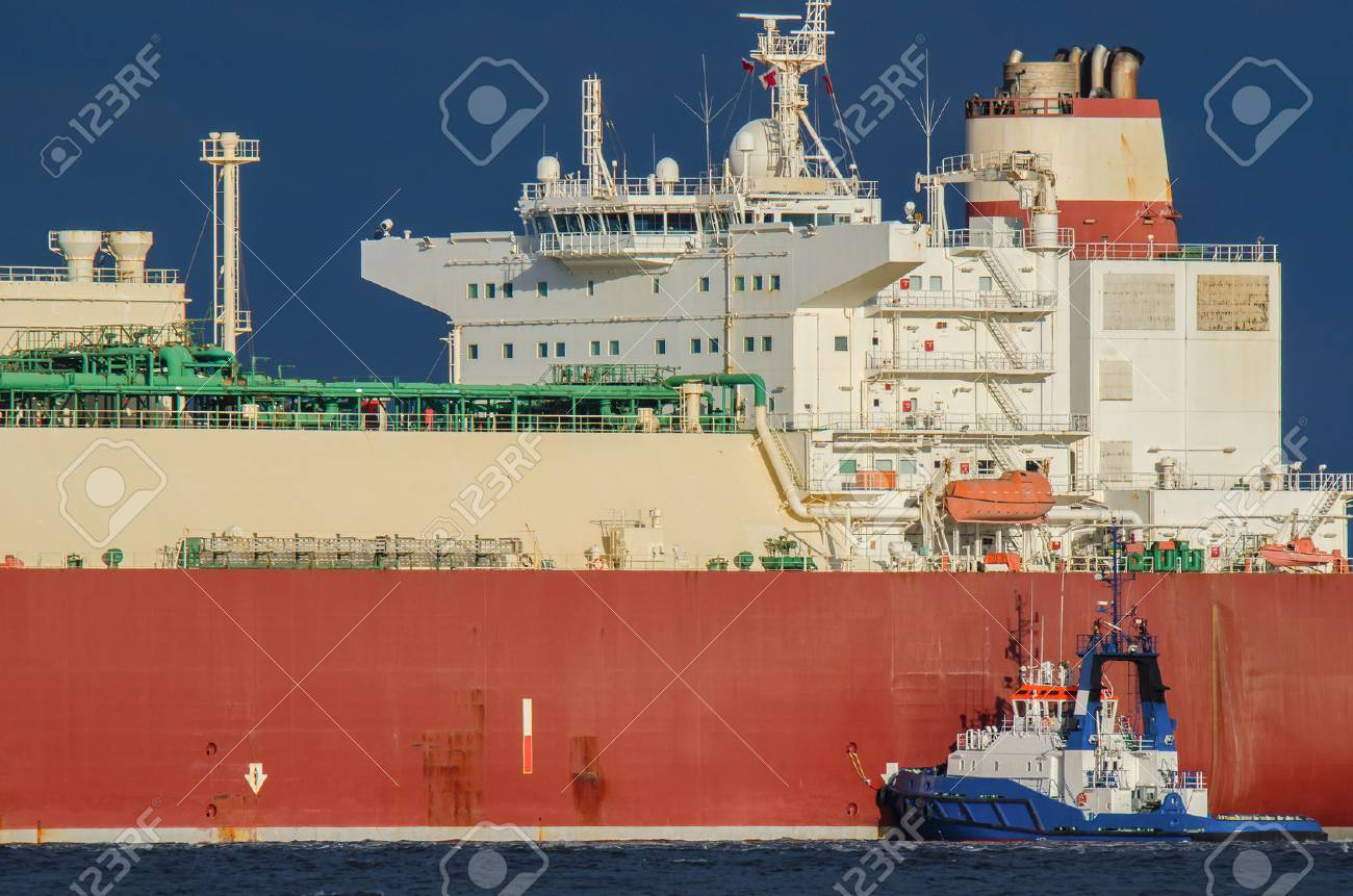 SWINOUJSCIE. Small tugboat helps to moor at the quay big lng tanker - 61547101