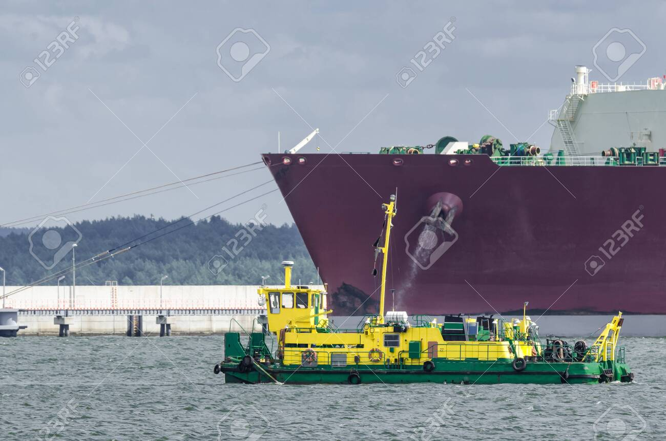 LNG TANKER - Ship moored to the gas terminal and dredger at work - 123523871