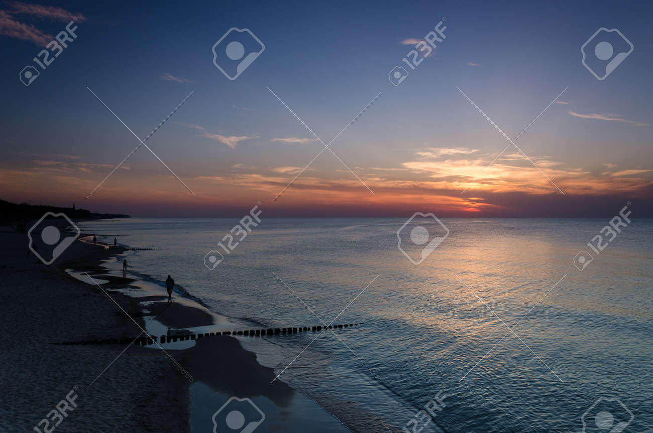 SUNSET OVER THE SEASHORE - People are walking on the beach - 169541029
