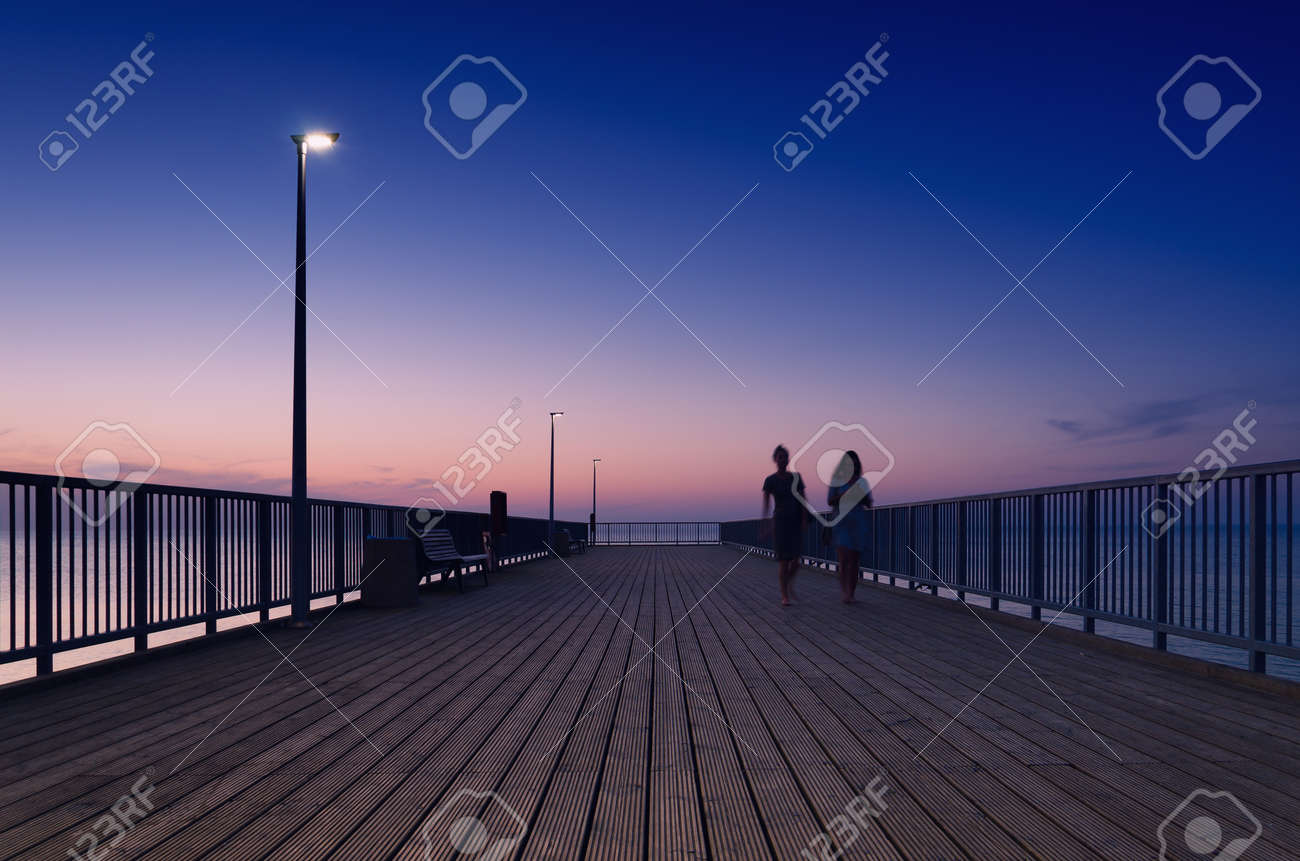 PIER ON THE SEA COAST - Womens walk at a quiet sunset - 169541035