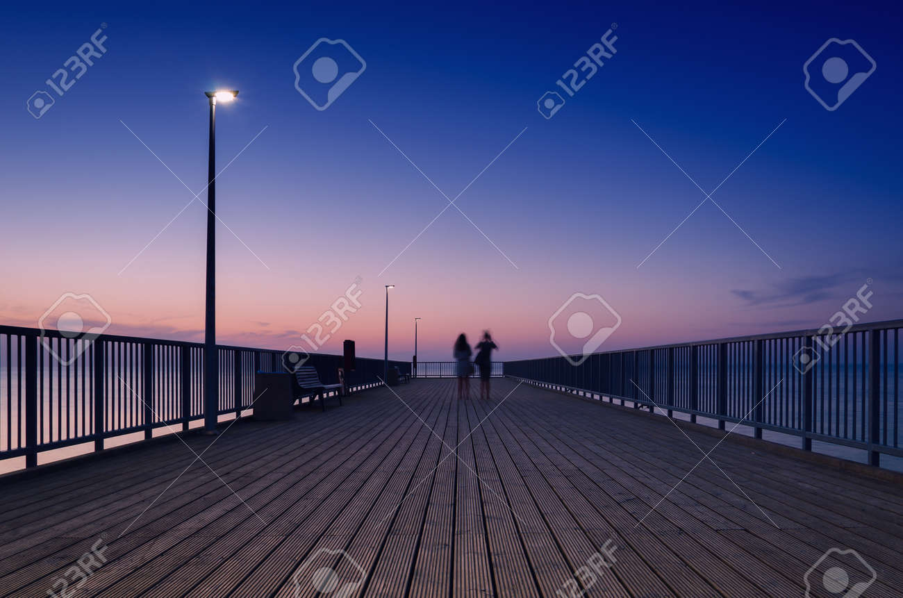 PIER ON THE SEA COAST - Womens walk at a quiet sunset - 169541105