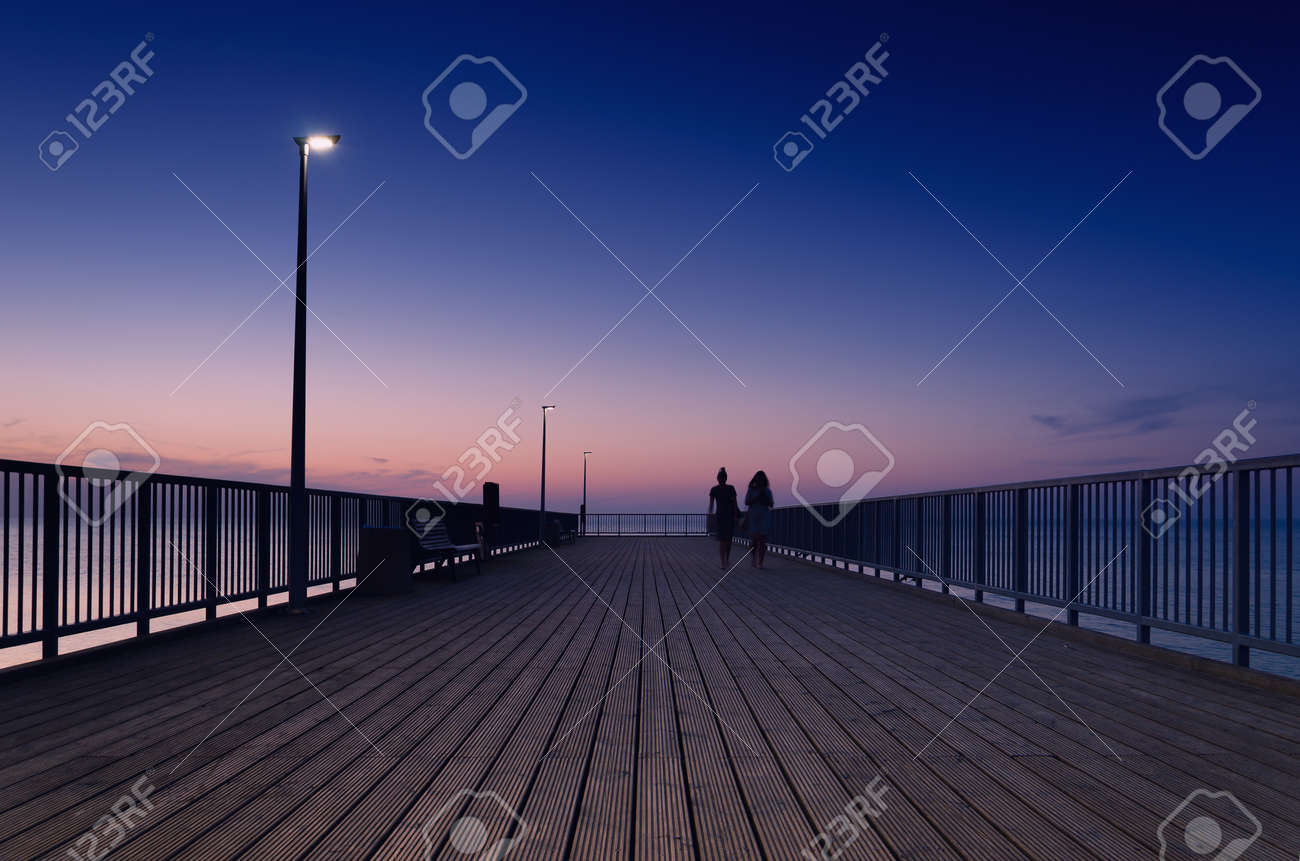 PIER ON THE SEA COAST - Womens walk at a quiet sunset - 169541136