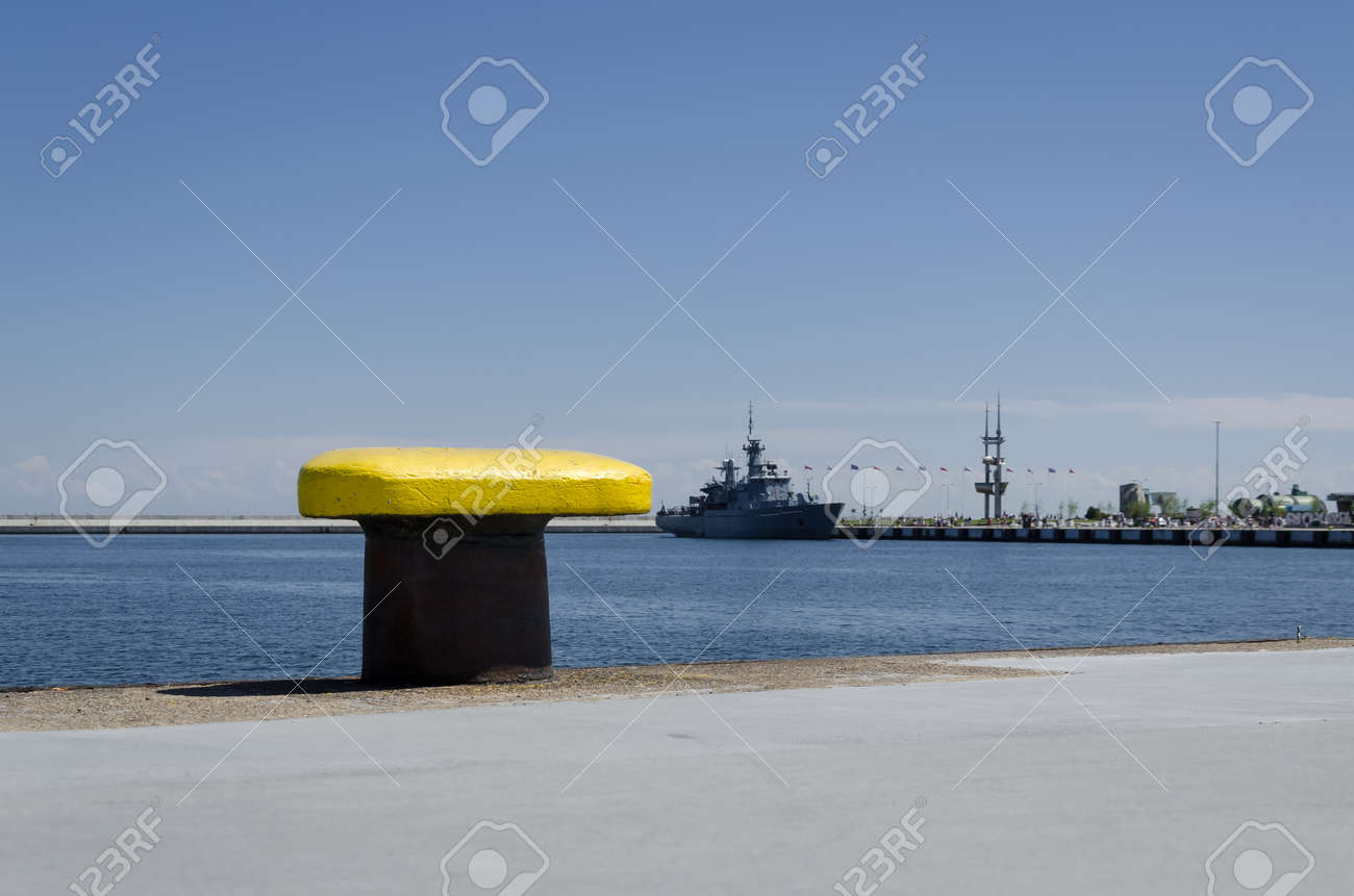 YELLOW BITT - Seaport wharf with warship in the background - 170448285