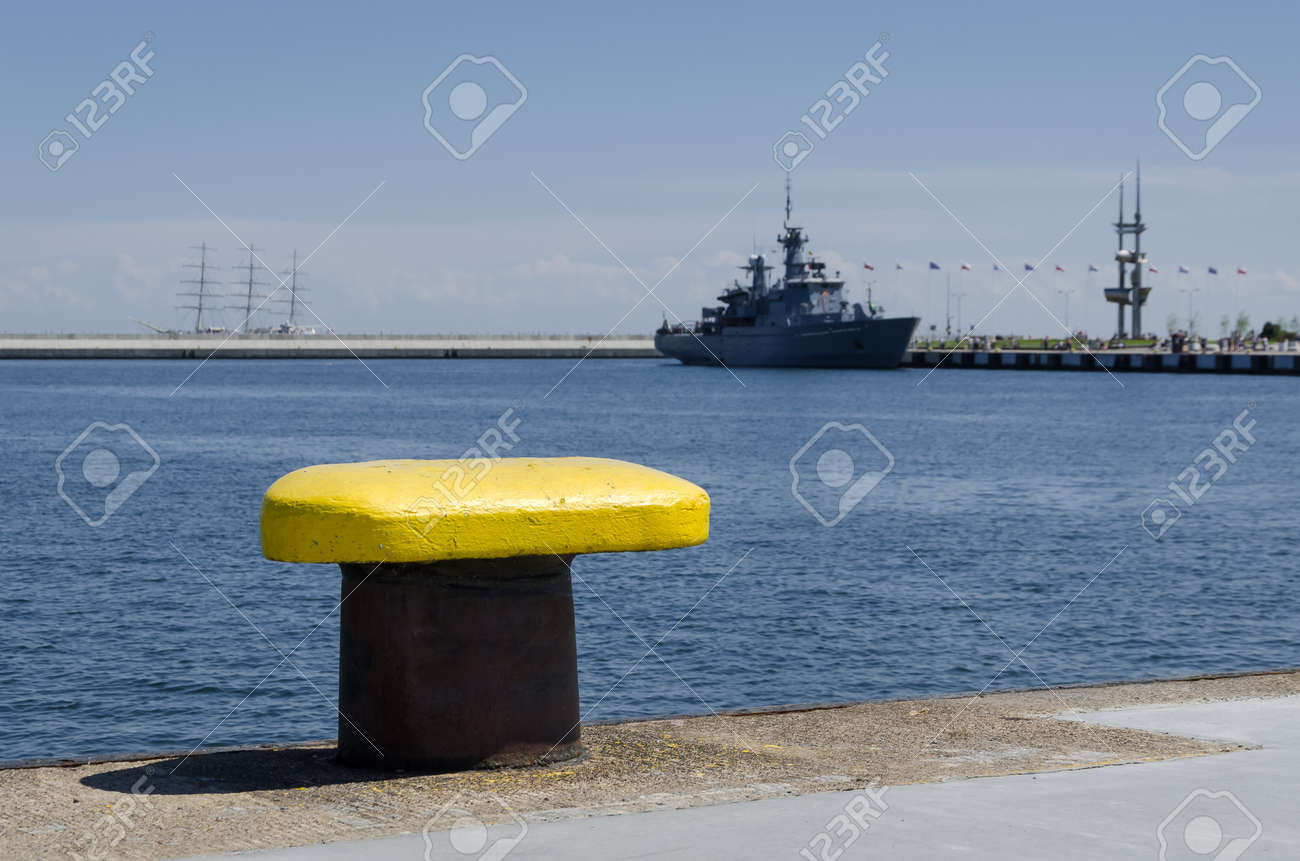 YELLOW BITT - Seaport wharf with warship in the background - 170381763