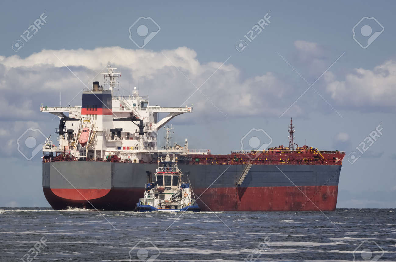 BULK CARRIER - The ship sails from port to sea secured by tug - 171046312