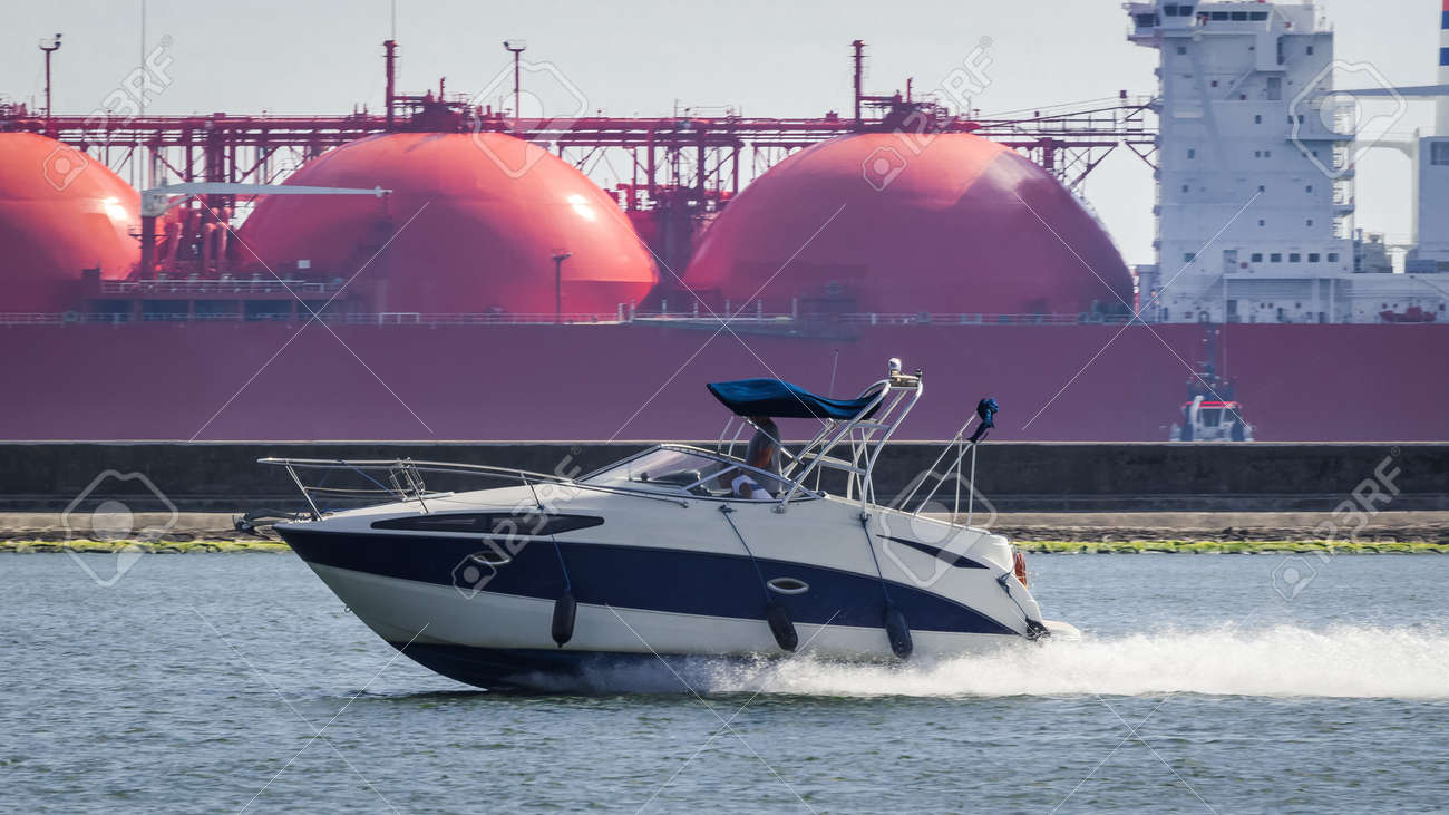 MOTORBOAT AND LNG TANKER - A recreational boat goes out to sea - 171648457
