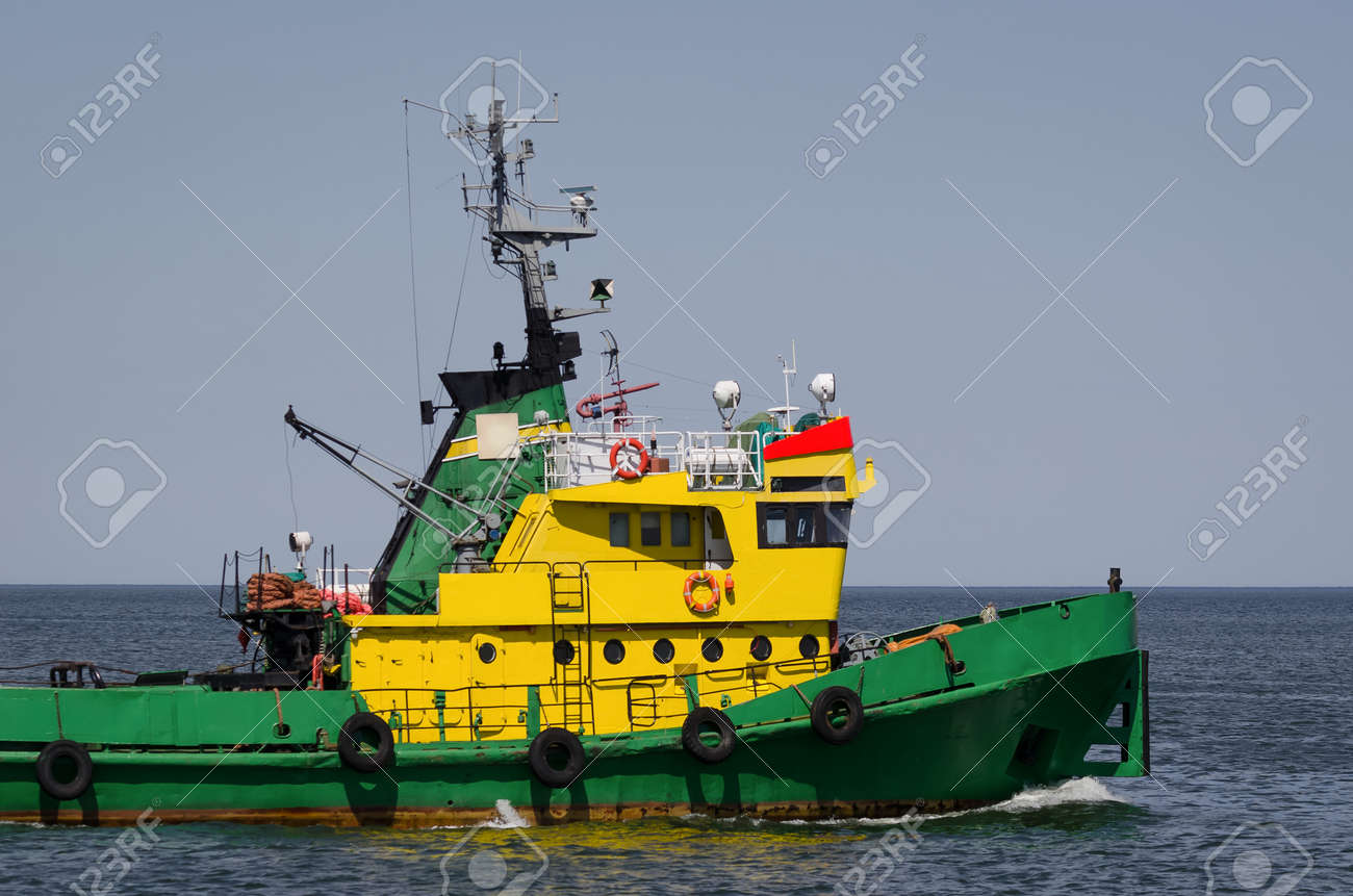 TUGBOAT - Auxiliary vessel is sailing on the background of breakwater - 171651617