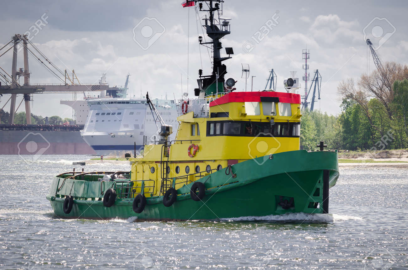 TUGBOAT - Auxiliary vessel sails in the seaport background - 171665922
