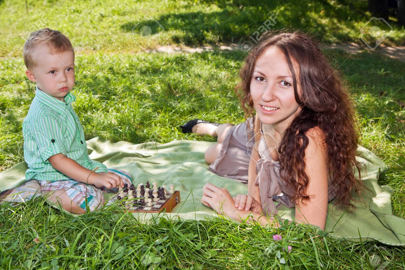 Mother teaches her son to play chess in the park Stock Photo - 12534167