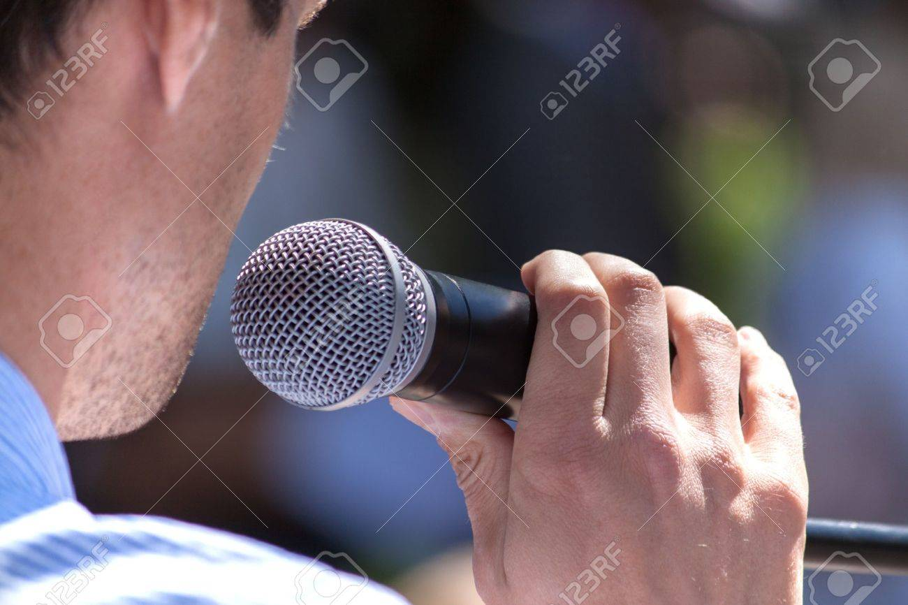 Speaker holds the microphone close up - 13884264