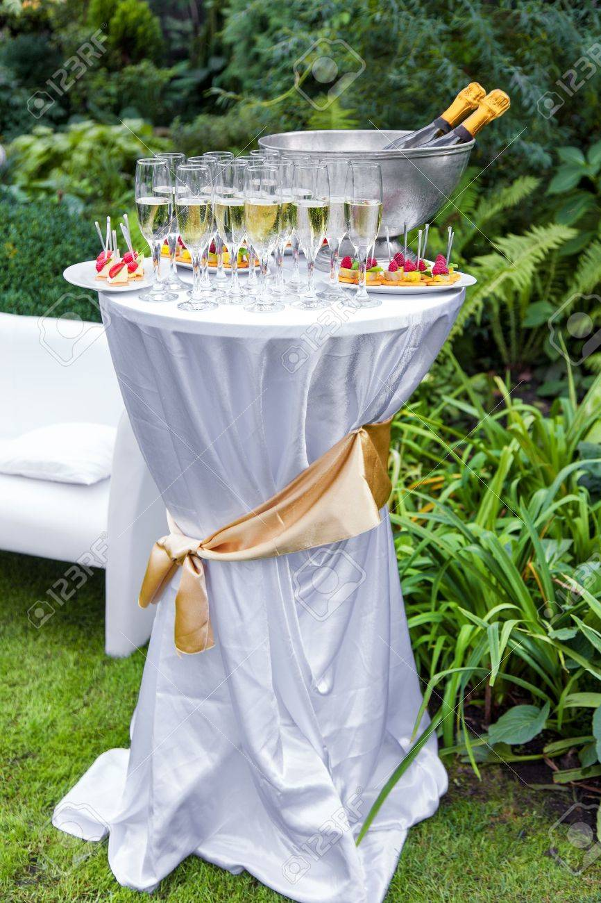 Table with champagne and appetizers at a wedding outdoors - 15257632