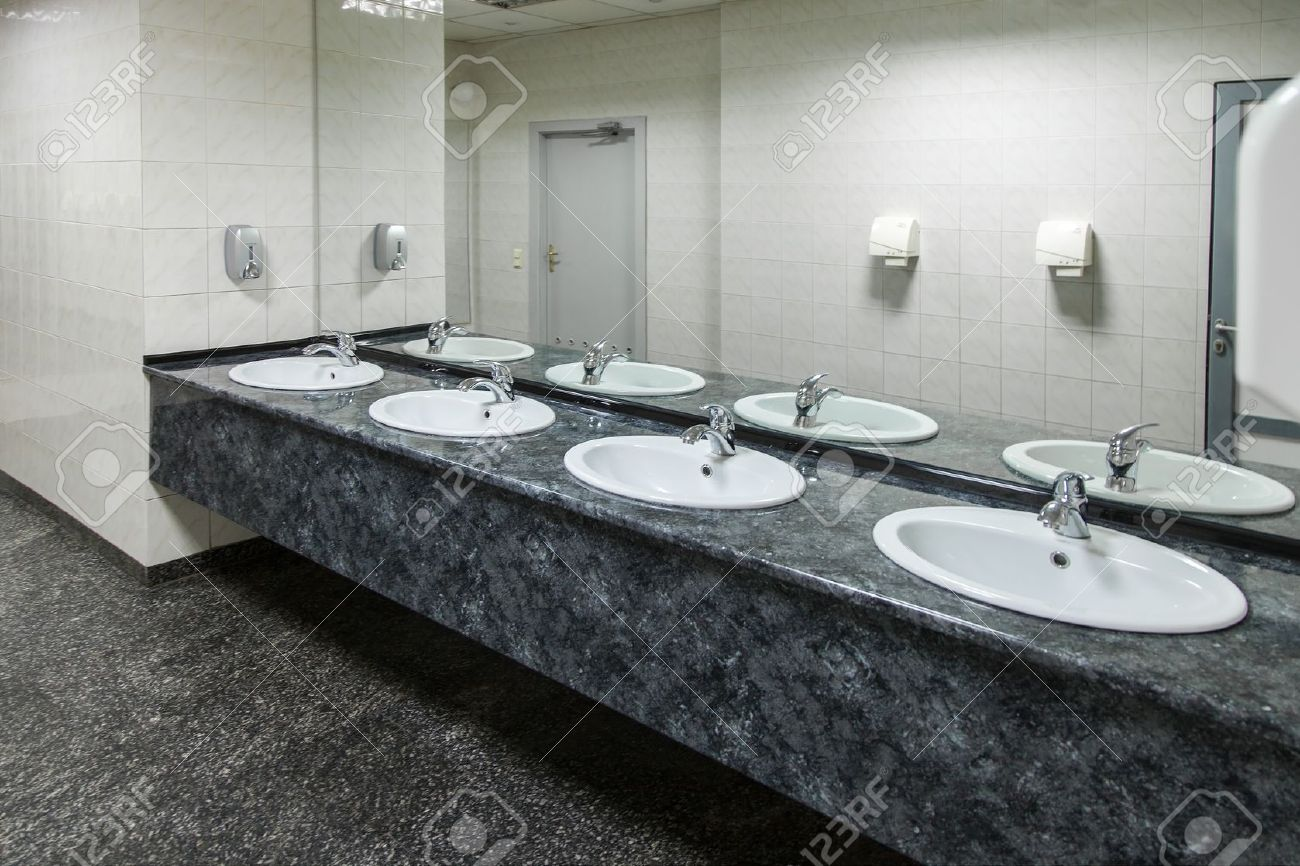 Row Of Wash Basins With Mirrors In Public Toilet Stock Photo