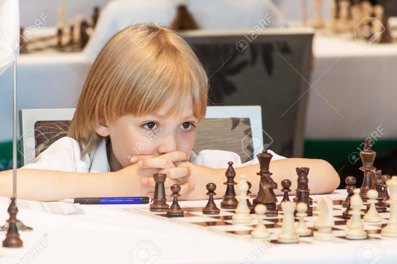 Young boy playing chess on the competitions - 20487182